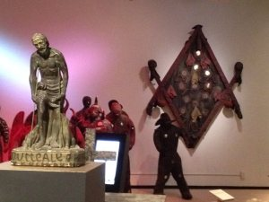 "Papa Legba to the left and a stylized symbol of ""Le Grand Mét"" on the wall at the Field Museum's Vodou exhibit. Life-sized Bizango Lwa, warrior spirits, appear in the background."