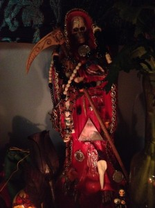 Detail of my La Santa Muerte Roja shrine. I beaded the main rosary draped across Her shoulder myself.