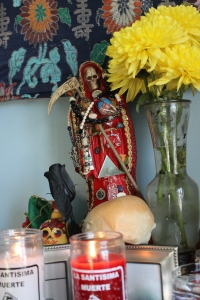 My La Santa Muerte Roja surveys Her offerings.