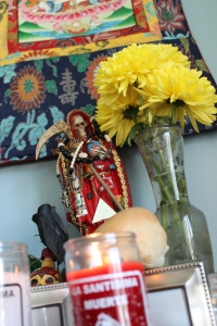 La Santa Muerte Roja loves Her offerings of flowers, bolillo bread rolls, clear water, incense, and tequila!
