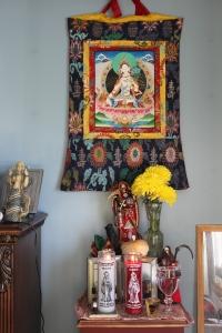 La Santa Muerte Roja's shrine capped with a White Tara thangka.