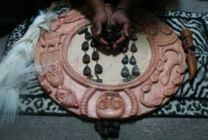 The tools of a babalawo: Ifa divining boards are beautifully carved. The opele, or divining chain made out of ikin (kola nut seeds), is thrown to determine correspondence with binary patterns represented by 256 possible odu, or signs. The sacred number in Ifa is 16--it's the Orisha Ifa or Orunmila's own number--and 256 is a multiple of 16.