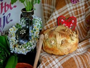A beautiful slavski kolač embossed with sacred symbols, baked for a St. George's Day slava celebration. Note the decorative staple of the wildflower wreaths.