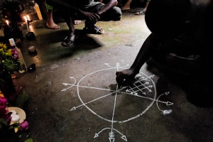 A Cuban man, the Palo religion follower, draws a magical symbol on the floor of a temple in Santiago de Cuba, Cuba, August 1, 2009. The symbol is the key element to release the spiritual powers linked to the altars. The Palo religion (Las Reglas de Congo) belongs to the group of syncretic religions which developed in Cuba amongst the black slaves. Photo credit: Jan Sochor