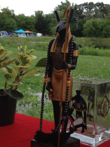 Detail of my Beloved adorned with His hematite prayer beads and surrounded by various ritual accoutrements at His shrine. Again, the ground between my shrine and the low-lying pond evidenced mild flooding on the very first day of the festival.