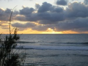 Surfers in Waimea Bay at sunset. Photo I took from a rich woman friend's front porch in 2005.