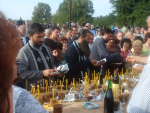 Singing dirges for the dead in a cemetery-wide parastos ceremony. Note all the little cups of žito to serve to the dead with lit beeswax candles in them. Photo credit: Kurir, Republika Srpska.