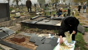 Kosovar Serbs commemorate Zadušnice amidst the vandalized graves of their deceased relatives in Kosovska Mitrovica. Note the eggs and grapes this widow is placing on her husband's grave, ritual foods symbolizing the life force and resurrection. As with widows in other countries where Eastern Orthodox Christianity is the dominant religion--Greece, Russia, Bulgaria, etc.--Serbian widows wear all black for the rest of their lives. Photo credit: Novosti, Republika Srpska.
