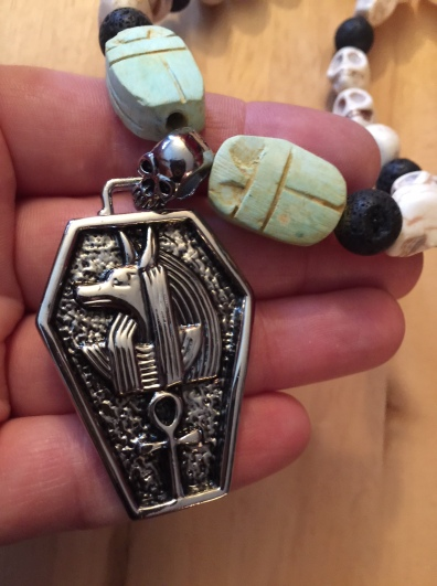 Stainless steel Anubis in a coffin pendant with ankh flanked by Egyptian scarab, pumice stone, and white howlite skull beads. Kemetic Goth for the win!